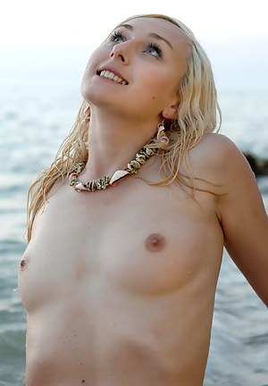 Sexy nude blonde having fun on seashore spreading her legs and showing her beauty