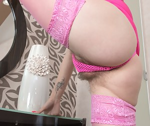 Ira loves pink, and has on her pink dress, pink stockings, and heels. She undresses and has a hairy pussy under her pink panties. She retires to her bed, starts to masturbates and enjoying herself.