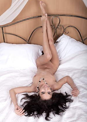 Stunning girl with splendid dark hair and gorgeous figure gets nude on a bed and teases.
