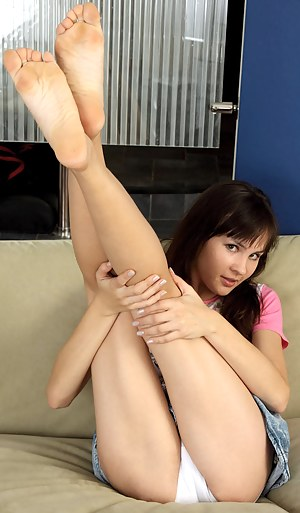 Sexy Nubile Jasha posing off her medium sized tits while teasing on the sofa