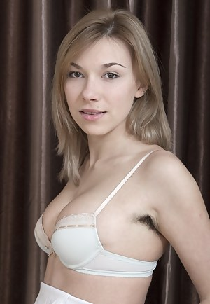 Alisia stands doing her makeup wearing her white dress and stockings. On her bed, she slowly takes off her clothes and is breathtaking. She gives us a full view of her hairy pits and hairy pussy and is sexy.